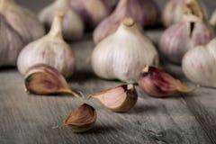 Lampadine dell'aglio del primo piano e chiodi di garofano di aglio su fondo di legno aglio Aglio fresco Immagini Stock