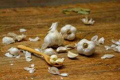 Lampadine dell'aglio e chiodi di garofano di aglio sulla tavola rustica di legno immagine stock