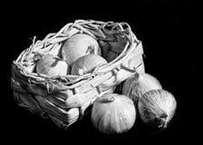 Lampadine dell'aglio in un canestro di vimini isolato sul nero Fotografia Stock Libera da Diritti