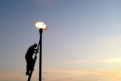 Lampadine dell'iluminazione pubblica della riparazione dell'elettricista e scalare su una scala fotografia stock libera da diritti