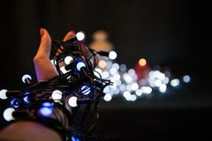 Lampadine di Natale in mani Fotografia Stock