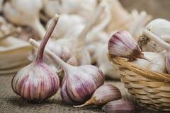 Lampadine e chiodi di garofano di aglio organico naturale su una stuoia di tela ed in una fine casalinga del canestro su fotografie stock libere da diritti