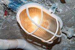 Lampan hänger i källaren av huset, lampan är i ett skyddande fall royaltyfria foton