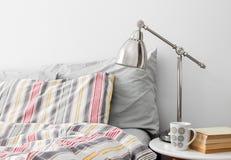 Lampan och böcker på en sida bordlägger nära säng arkivfoto