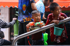 LAMPANG, ТАИЛАНД - 13-ОЕ АПРЕЛЯ 2011: В фестивале Songkran люди снесут танк воды на приводе тележки thair вокруг города Стоковая Фотография RF