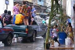 LAMPANG, ТАИЛАНД - 13-ОЕ АПРЕЛЯ 2011: В фестивале Songkran люди снесут танк воды на приводе тележки thair вокруг города Стоковые Изображения RF
