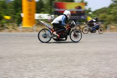 LAMPANG, THAÏLANDE - 24 AVRIL 2010 : Cavalier de moto emballant le vélo d'entrave photo libre de droits