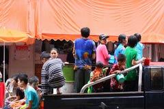 LAMPANG THAILAND - 13 APRIL 2011: I den Songkran festivalen ska folket bära behållaren av vatten på thairlastbildrev runt om stad Arkivfoto