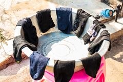 LAMPANG, THAILAND - On January 11, 2019: Laundry socks outdoor in the villagers` old stainless steel tanks, placed on pink plasti stock photos