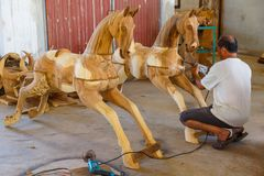 Production of carved wooden animal sculpture. Lampang, Thailand - November 3, 2012: Craftsman polishing wooden horse sculpture with polishing machine for Royalty Free Stock Photography