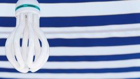 Lampe économiseuse d'énergie blanche sur le fond blanc-bleu images stock