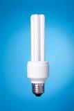Lampe économiseuse d'énergie sur le fond bleu Images stock