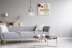 Lampe über grauem Sofa mit Kissen im hellen Wohnzimmerinnenraum mit Plakat und Tabelle Reales Foto lizenzfreie stockbilder