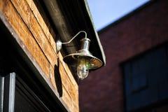 Lampe antique avec une ampoule sur un conseil en bois au-dessus de la porte photo libre de droits