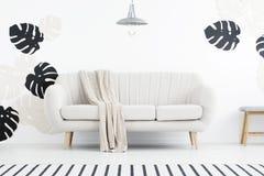 Lampe au-dessus de divan avec la couverture dans l'intérieur blanc de salon avec photo libre de droits