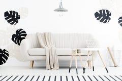 Lampe au-dessus du divan blanc avec la couverture dans l'intérieur de salon avec photographie stock