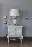 Lampe auf einem weißen ursprünglichen Nachttisch Lizenzfreie Stockbilder