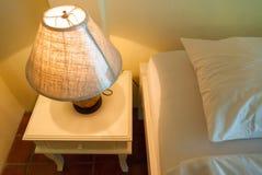 Lampe auf einer Nachttabelle nahe bei einem Bett lizenzfreie stockfotografie