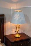 Lampe avec un abat-jour dans le style classique dans la chambre à coucher Images stock