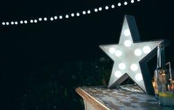 Lampe blanche d'étoile avec les ampoules au-dessus de la table en bois Photos libres de droits