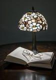 Lampe, Buch und Gläser stockfoto