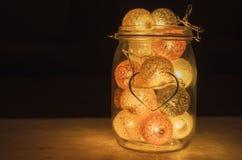 Lampe créative faite de boules de coton dans le pot en verre avec le signe du hea Photo stock