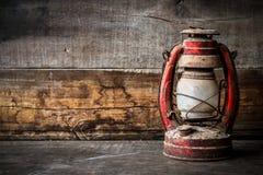 Lampe démodée de lanterne d'huile de kérosène de vintage brûlant avec une lumière molle de lueur avec le plancher en bois âgé Photo stock