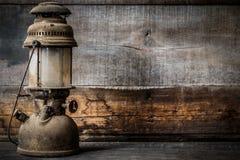 Lampe démodée de lanterne d'huile de kérosène de vintage brûlant avec une lumière molle de lueur avec le plancher en bois âgé Image stock