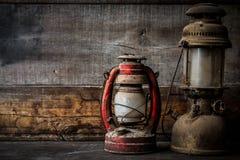Lampe démodée de lanterne d'huile de kérosène de vintage brûlant avec une lumière molle de lueur avec le plancher en bois âgé Photographie stock