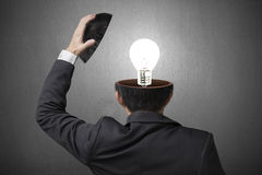 Lampe d'éclairage à l'intérieur de tête d'homme d'affaires dans le backgroun concret gris Photo stock
