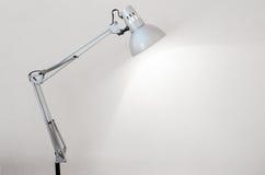 Lampe de bureau illuminant un mur en béton blanc Photo stock