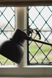lampe de table noire dans l'intérieur contre la fenêtre avec des losanges Concept d'affaires ou d'éducation avec l'endroit pour v photographie stock