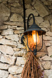 Lampe der Weinlese im Freien mit trockenen Blumen auf dem Steinwandhaus Stockfotografie
