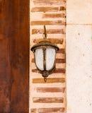 Lampe, die auf einer Backsteinmauer hängt Lizenzfreie Stockfotos