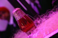 Lampe en verre rouge avec le métal ouvré d'isolement avec le fond de tache floue photo stock