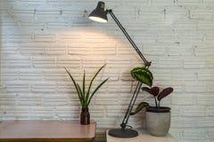 Lampe et pot modernes sur le bureau sur le fond blanc de mur Image libre de droits