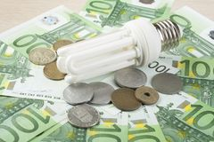 Lampe fluorescente économiseuse d'énergie sur le fond d'argent, l'ampoule d'Eco, la comparaison des lampes économiseuses d'énergi Photographie stock libre de droits