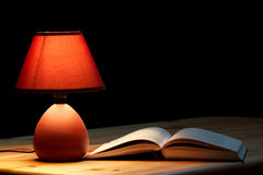 Lampe illuminant un livre Image libre de droits