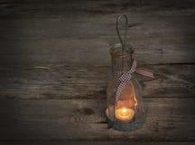 Lampe-Laterne mit einer Kerze auf hölzernem Hintergrund Stockbilder