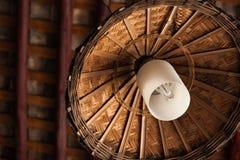 Lampe mit dem Bambuslampenschirm, der unter dem Dach hängt Stockfotos