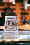 Lampe mit einer Kerze auf dem Tisch stehend stockfotografie