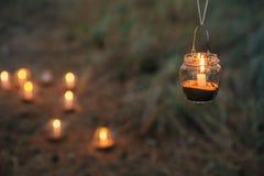 Lampe mit Kerze hängt an einem Baum nachts Nah heiraten Stockfotografie