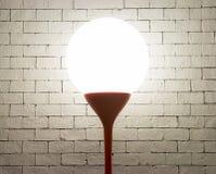 Lampe mit Kreisform auf weißem Ziegelsteinhintergrund Stockfotografie
