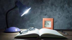 Lampe mit Notizbuch, Stift, Uhr und Gläsern auf Holztisch mit Stockbilder