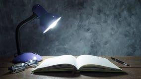 Lampe mit Notizbuch, Stift und Gläsern auf Holztisch mit vintag Stockfotos