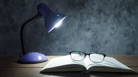 Lampe mit Notizbuch und Gläsern auf Holztisch mit Weinlese wa Stockfoto