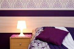 Lampe mit violetten Themaschlafzimmerdetails Stockbilder
