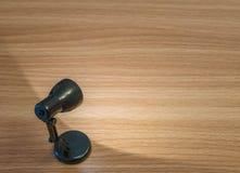 Lampe noire de plan rapproché la petite avec la lumière dans la chambre noire sur le bureau en bois a donné au fond une consistan Photographie stock libre de droits
