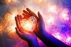 Lampe orange en pastel molle dans les paniers en bambou dans la forme de coeur sur la main deux Image libre de droits
