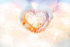 Lampe orange en pastel molle dans les paniers en bambou dans la forme de coeur sur la main deux Photos libres de droits